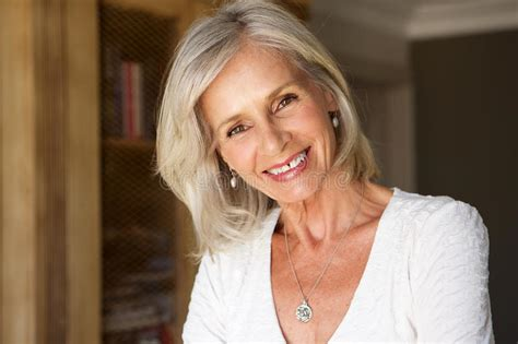 Beautiful Older Woman Standing In Study Smiling Stock